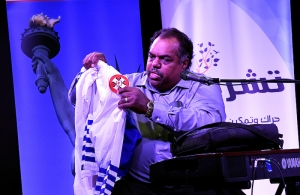 Daryl Davis holding up KKK robes at Blues and Rock for Humanity in November 2017.