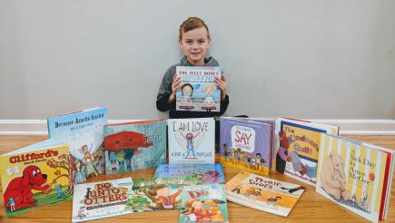 Garett shows off the kindness books for his Kindness Corner.