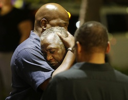 Worshippers embrace following a group prayer across the street from the scene of a shooting Wednesday, June 17, 2015, in Charleston, S.C.