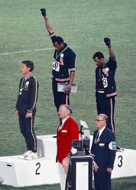 American sprinters Tommie Smith (center) and John Carlos raise black-power fists at the 1968 Mexican Olympic games.