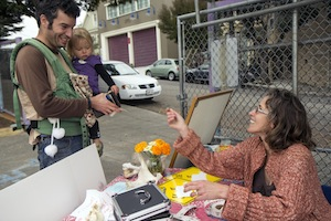 "Karen Curtiss takes a donation at Junipero Serra Elementary's annual fundraiser. Though her family's culture, language, education and income make them a minority at the predominately poor and Latino school, Curtiss said she feels intense loyalty to its community: ""We believe in our family being part of a complete community, and not a socioeconomic bubble."""