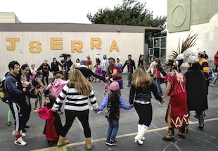 "A Central American indigenous dance troupe from UC Berkeley, leads a ""friendship dance"" at Junipero Serra's he annual Halloween-Día de los Muertos celebration. Most of Junipero Serra's students are immigrants or the children of immigrants, mainly from Latin America. So all gatherings are conducted in both Spanish and English, and parents in both groups make a conscious effort to build community across cultural and linguistic barriers, Principal Evelyn Cheung said. ""These are not isolated groupings. They work together and they've built trust."""