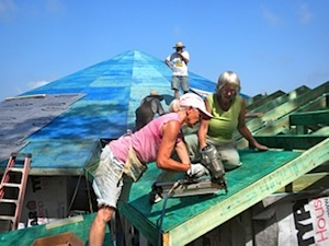 Vonda Frantz (foreground, in pink shirt) putting the roof on the common house for Potluck Farm's new Elderberry community.
