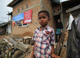 A boy stands outside his home following the devastating 2009  earthquake in Padang, Indonesia.
